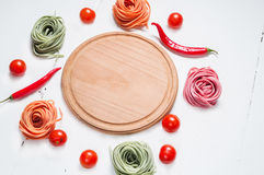 Colorful rolled pasta, cherry tomatoes on the white wooden background Royalty Free Stock Images