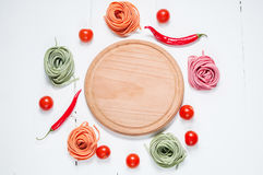 Colorful rolled pasta, cherry tomatoes on the white wooden background Royalty Free Stock Photo