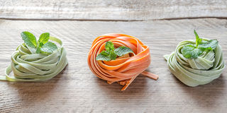 Colorful rolled pasta on the wooden background Stock Photos