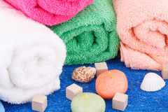 Towels. Colorful rolled towels with candles and shells closeup picture Royalty Free Stock Photos