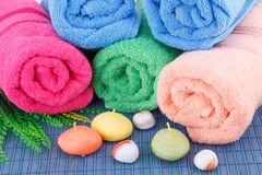Towels. Colorful rolled towels with leaves, soaps and stones closeup picture Stock Image