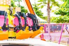 Colorful roller coaster seats at amusement park Stock Photos