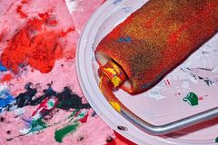 Colorful roller lying on the white plate after beign used for wall art painting stock image