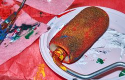 Colorful roller lying on the white plate after beign used for wall art painting royalty free stock image
