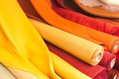 Colorful rolls of natural linen cloth. Lie on the market counter Royalty Free Stock Images