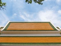 Colorful roof of the traditional Thai church. Colorful roof with the earthenware tile of the traditional Thai church,summer time under the clear blue sky Royalty Free Stock Image