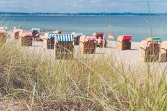 Colorful roofed chairs on sandy beach in Travemunde. Some grass in foreground. Germany Royalty Free Stock Photo