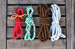Colorful rope with knots. On a rustic table royalty free stock photo