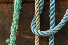Colorful rope used on a deep sea fishing trawler lay over the si. De of a rusted hulk Royalty Free Stock Photos