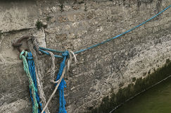 Colorful Ropes on the Seine River, Paris France. Blue and cyan ropes attached to a metal ring used to secure a barge on the Seine River in Paris, France royalty free stock photography