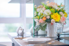 Colorful rose flower in vase on dinning table Royalty Free Stock Photos