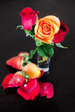 Colorful roses in a vase and strawberry on a wooden table Royalty Free Stock Images