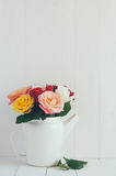 Colorful roses in white enamel coffee pot Royalty Free Stock Photos