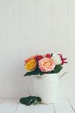 Colorful roses in white enamel coffee pot. Bouquet of fresh flowers, colorful roses in white enamel coffee pot, home decor in country style, painted white Royalty Free Stock Image