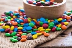 Colorful round chocolate candies on gunny sack cloth on wood table. Selective focus Stock Image