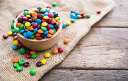Colorful round chocolate candies in wooden bowl on gunny sack cloth on wood table. With copy space Royalty Free Stock Image