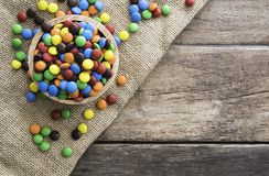 Colorful round chocolate candies in wooden bowl on gunny sack cloth on wood table. Top view, with copy space Royalty Free Stock Image