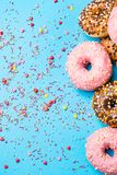 Colorful round donuts on blue background. Flat lay, top view. stock photos