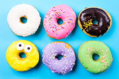 Colorful round donuts on blue background. Flat lay, top view. Royalty Free Stock Photo