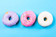Colorful round donuts on blue background. Flat lay, top view. Stock Photography