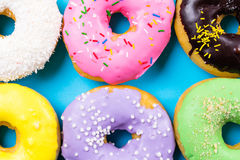Colorful round donuts on blue background. Flat lay, top view. Stock Image