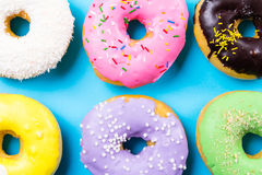 Colorful round donuts on blue background. Flat lay, top view. Stock Photo