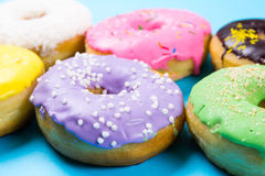 Colorful round donuts on blue background. Flat lay, top view. Stock Images