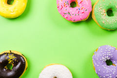 Colorful round donuts on green background. Flat lay, top view. Royalty Free Stock Photography