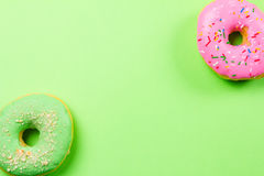 Colorful round donuts on green background. Flat lay, top view. Stock Photography