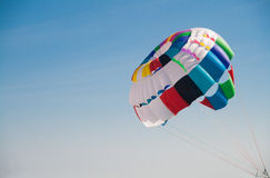 Colorful round parachute against the blue sky Stock Photo