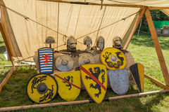 Colorful round shields, conical helmets displayed on medieval summer festival Royalty Free Stock Images