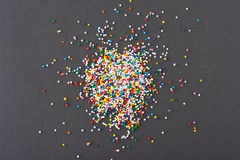 Colorful round sprinkles spilled on black background, isolated Stock Image