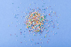 Colorful round sprinkles spilled on blue background, isolated Royalty Free Stock Photos