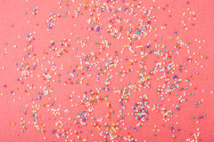 Colorful round sprinkles spilled on red background, isolated Royalty Free Stock Photo