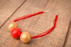 Colorful round wood beads necklace hand painted with golden and red color beads on a wood table Stock Images