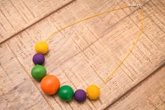 Colorful round wood beads necklace hand painted with yellow, purple, green and orange color beads on a wood table Royalty Free Stock Image