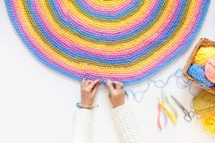 Colorful round yarn mat. Yarn in coils and tangles. A woman knit. Crocheted home bright colored mat. Rainbow yarn in the basket. Hooks for knitting Royalty Free Stock Image