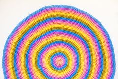 Colorful round yarn mat. Yarn in coils and tangles. A woman knit. Crocheted home bright colored mat. Rainbow yarn in the basket. Hooks for knitting Royalty Free Stock Photography