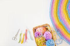 Colorful round yarn mat. Crochet. Yarn in coils and tangles. Whi. Crocheted home bright colored mat. Rainbow yarn in the basket. Hooks for knitting Royalty Free Stock Images