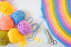 Colorful round yarn mat. Crochet. Yarn in coils and tangles. Whi. Crocheted home bright colored mat. Rainbow yarn in the basket. Hooks for knitting Stock Photos