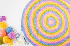 Colorful round yarn mat. Crochet. Yarn in coils and tangles. Whi. Crocheted home bright colored mat. Rainbow yarn in the basket. Hooks for knitting Stock Photo