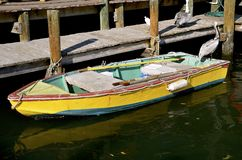 Colorful row boat and pelicans at a dock Stock Photo