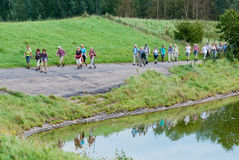 A colorful row of hikers along a Dutch lakeside. Hike along the shores of the Markiezaatsmeer near the city of Bergen op Zoom (North-Brabant) in the Netherlands Royalty Free Stock Images
