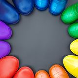 Colorful rubber boots of all colors of the rainbow-red, orange, yellow, green, blue, cyan and purple stand on the gray surface in. A circle. Top view, space for royalty free stock photo