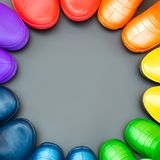 Colorful rubber boots of all colors of the rainbow-red, orange, yellow, green, blue, cyan and purple stand on the gray surface in. A circle. Top view, space for royalty free stock photos
