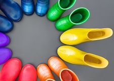 Colorful rubber boots of all colors of the rainbow-red, orange, yellow, green, blue, cyan and purple stand on the gray surface in. A circle. Top view, space for stock photo