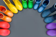 Colorful rubber boots-red, orange, yellow, green, cyan, blue and purple stand in the shape of a rainbow . Top view, space for text royalty free stock image