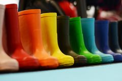 Colorful rubber rain boots for kids on the shelf of a store, waterproof footwear for fall royalty free stock photography