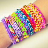 Colorful rubber rainbow loom band bracelets on wrist. Trendy kids fashion accessories.  Vintage retro tonal photo filter correction Stock Photography
