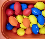 Colorful rubber rugby balls in orange bucket. stock image